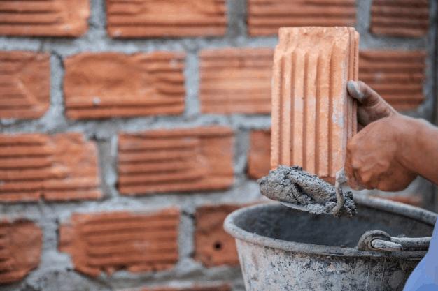 trabalhador de alvenaria com pá de pedreiro